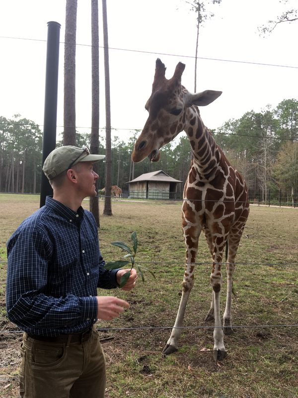Jim with a giraffe at White Oak Conservation Center
