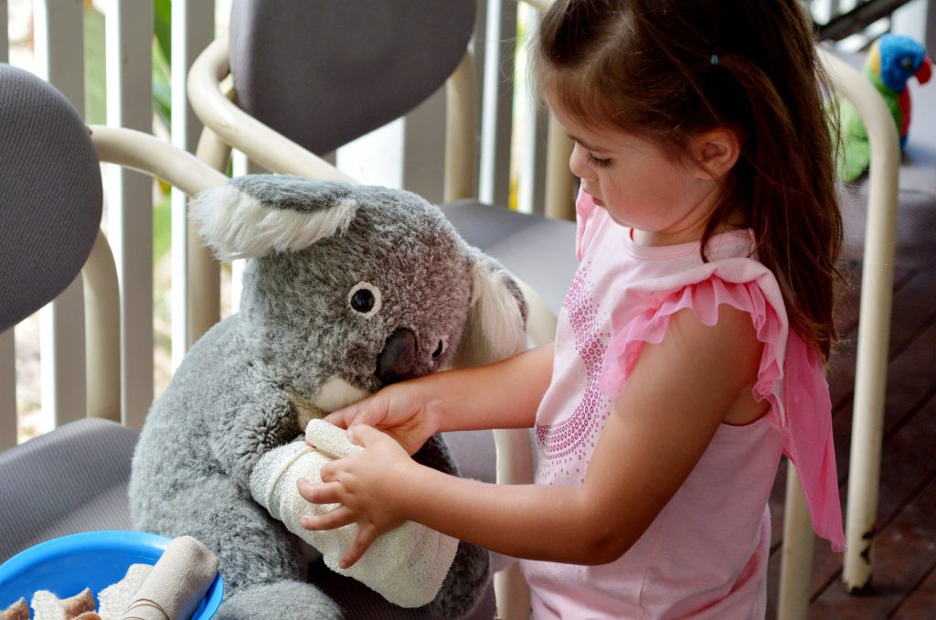 Little girl play pretend to be animal doctor (Veterinary physician), placing a bandage over an arm of injured Koala soft toy doll.